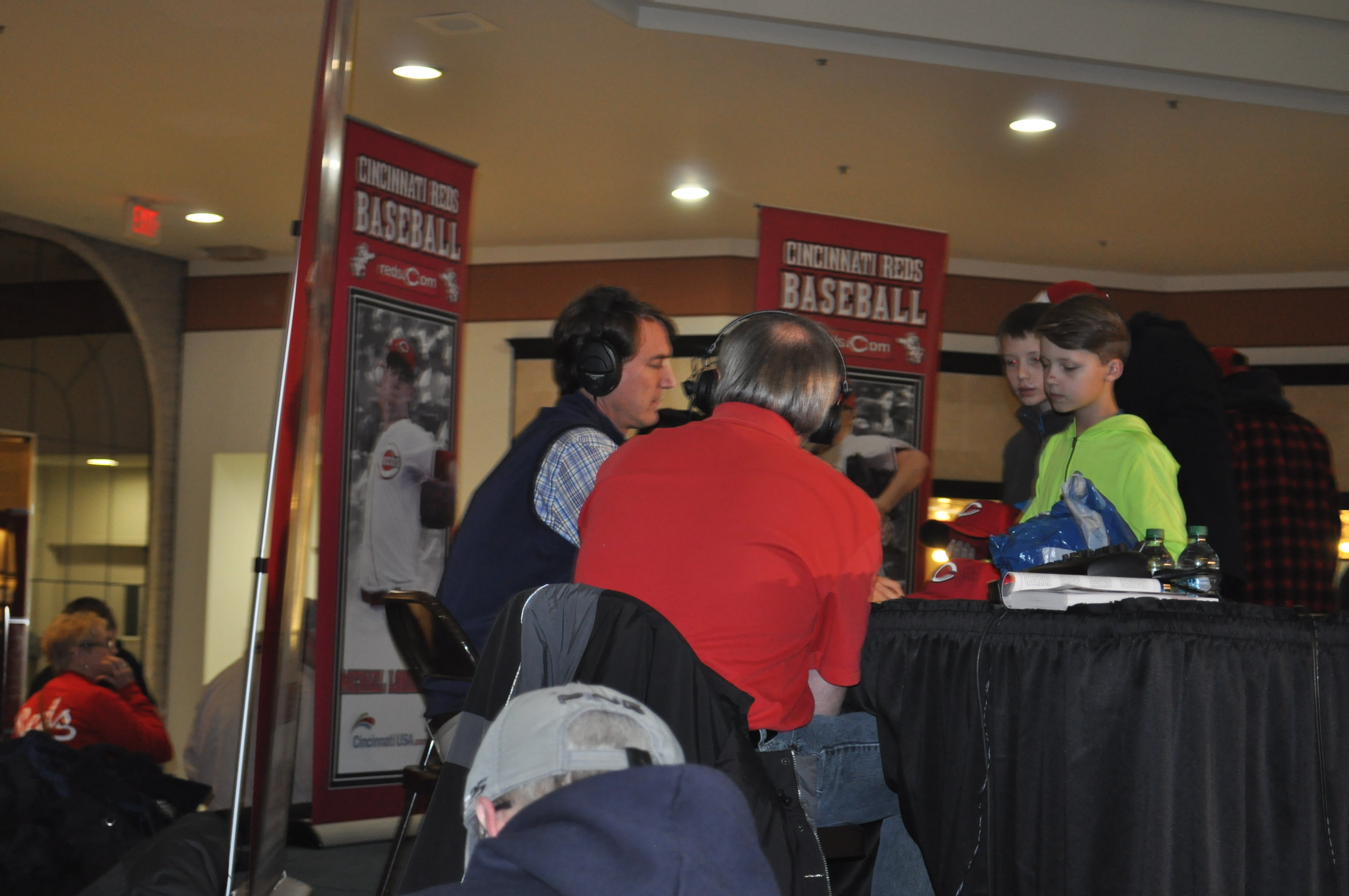 Reds GM Dick Williams signing autographs for some young fans while being interviewed by WCHS-AM Radio 580 sportscaster Jeff Jenkins.
